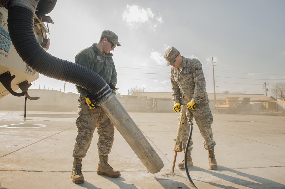 Airman 1st Class Jacob Fetters, left, and Airman 1st Class Brendan Kinser, 374th Civil Engineer Squadron pavement and equipment technician, perform a spot repair on a section of Yokota Air Base, Japan, Jan. 13, 2016. From shovels and jackhammers to cranes and bulldozers, the duties of the 'Dirt Boys' require them to be experts of a wide assortment of machinery. (U.S. Air Force photo by Airman 1st Class Delano Scott/Released)