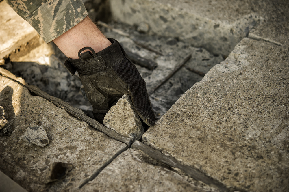Airman 1st Class Connor Harrington, 374th Civil Engineer Squadron pavement and equipment apprentice, removes a section of concrete from a spall repair site on Yokota Air Base, Japan, Jan. 13, 2016. Aptly named 'Dirt Boys', 374 CES pavement and equipment Airmen perform spall repairs as part of their preventative maintenance practices to ensure Yoktoa's airfield is free of cracks and tears. (U.S. Air Force photo by Airman 1st Class Delano Scott/Released)