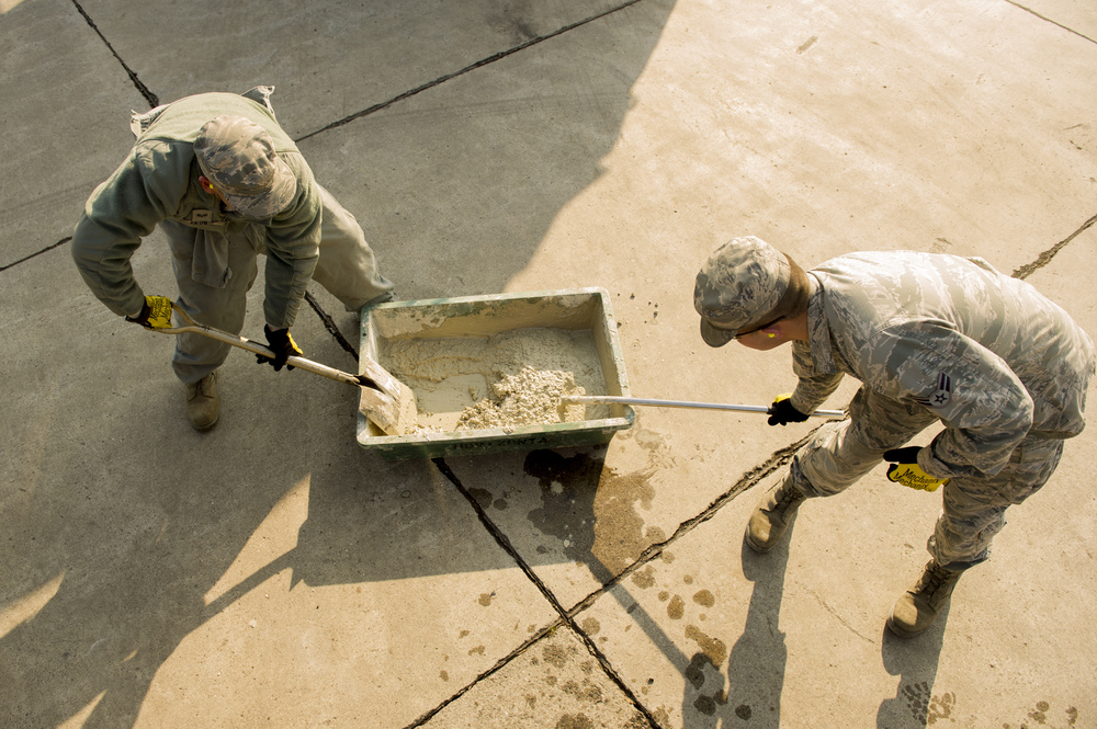 Senior Airman Tommy Zeus, left, and Airman 1st Class Brendan Kinser, 374th Civil Engineer Squadron pavements and heavy equipment technicians, prepare to perform a spot repair at Yokota Air Base, Japan, Jan. 13, 2016. As their job requires them to be experts with a wide assortment of machinery, the Airmen referred to as 'Dirt Boys' are able to assist other shops and squadrons around base. (U.S. Air Force photo by Airman 1st Class Delano Scott/Released)