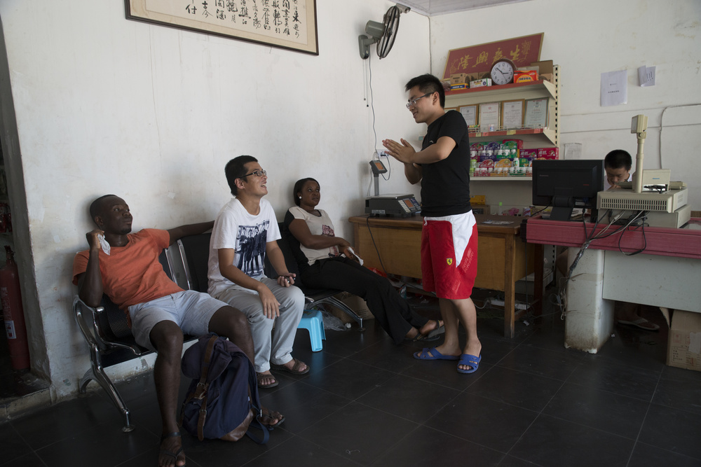 The owner, Hui, of the Jia Hua grocery store speaks with customers after the morning rush.