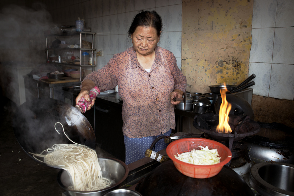 A Chinese mother and daughter have owned and operated the Hunan Restaurant for over fifteen years, located in Osu in greater Accra. A TV in the restaurant plays Chinese soap operas while the two women take a break from plucking chickens and preparing the dinner.