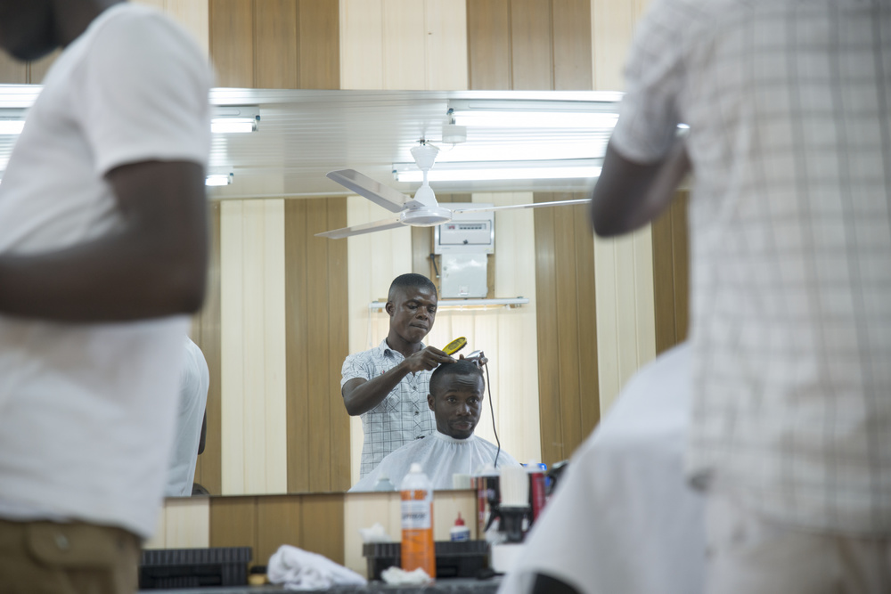 Kwame Otu gets a hair cut at Men's Clipperz barbershop in Osu.