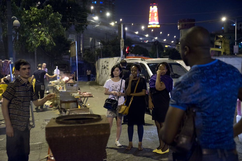The stifling hot weather of southern China deters people from the Xiao Bei market until late into the evening. Once the temperature cools, Chinese vendors come out to sell goods to Africans. Chinese police stand guard, checking African visas while video cameras placed throughout the area keep watch.