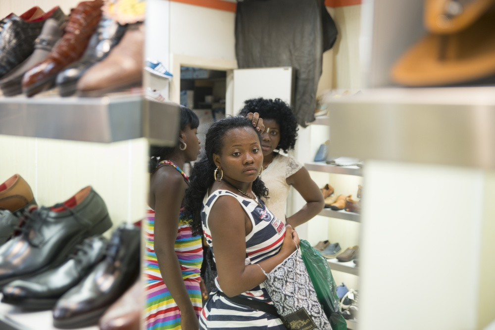 Three women, Chanceline, Joyce, and Shadai, from Angola window shop in the Xiao Bei market.