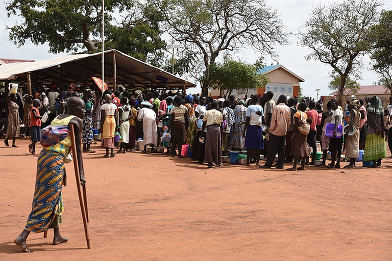 People line up at the food distribution center at Nyumanzi refugee transit center near Adjumani, Uganda on 23 September 2016. Since the escalation of violence in South Sudan in July, one million South Sudanese refugees have fled into neighboring countries, with over 373,000 in Uganda. Nyumanzi refugee transit center houses 3,474 refugees who will be transferred to the nearby settlement next week.