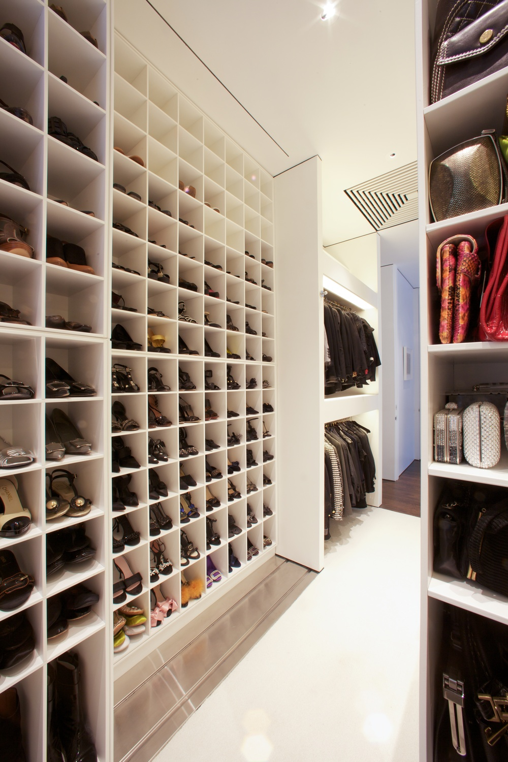Master closet with rolling shoe storage.