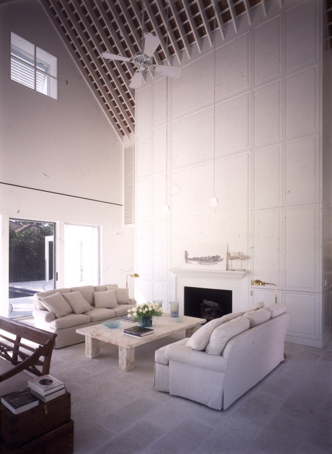 Delicate wood paneling frames the fireplace.