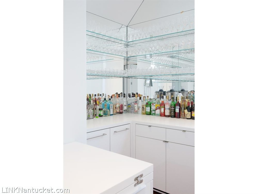 A corner closet bar adored in starphire mirror.