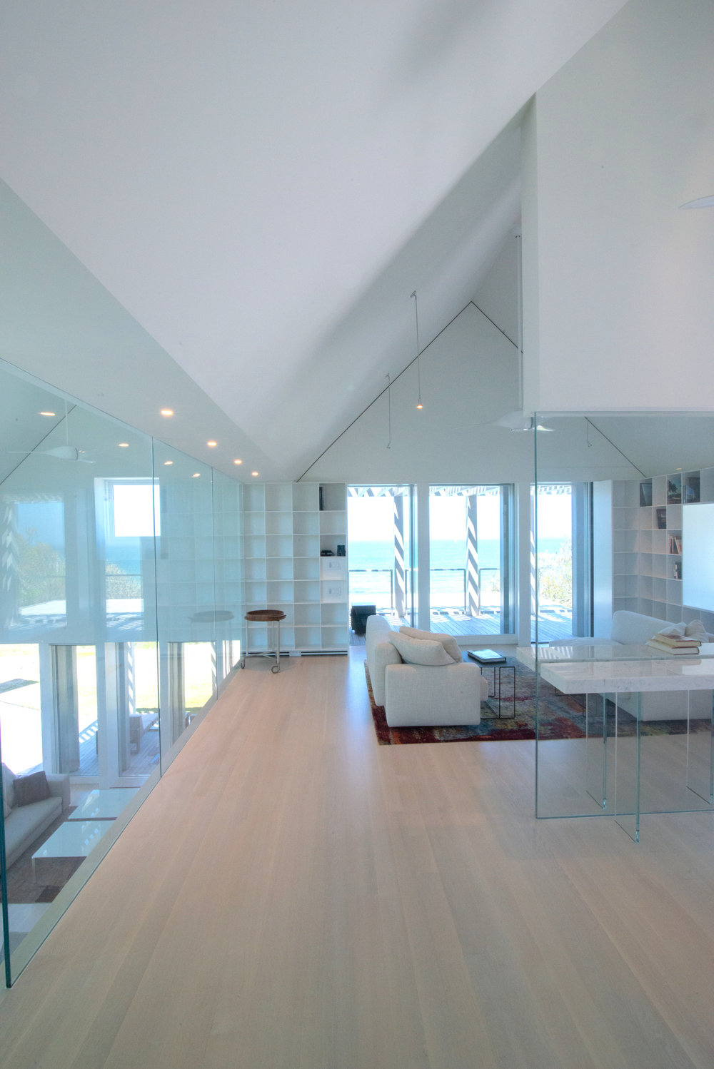 A glass enclosed upper living room over looks the lower floors of this Martha's Vineyard seaside cottage.