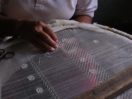 An embroiderer works on her calado