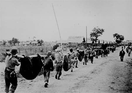 Filipino soldiers march as POWs carrying their dead on a country road in the Philippines