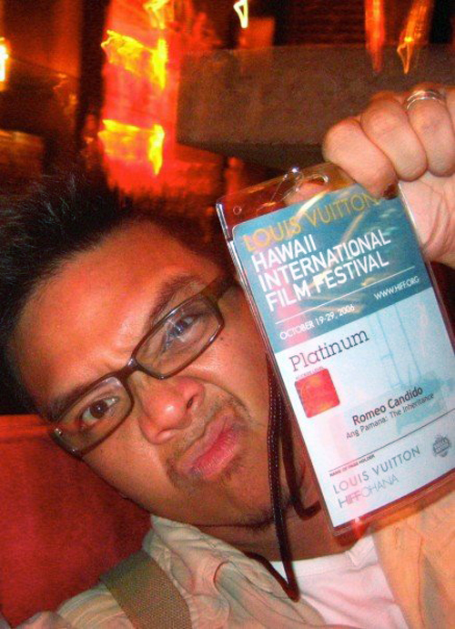 Romeo holds up his film festival pass to the camera making a funny face.