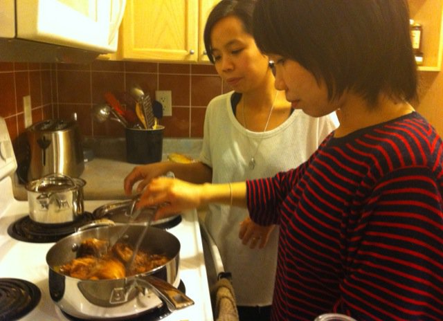 Casey and I combining our cooking over a simmering pot of delicious adobo
