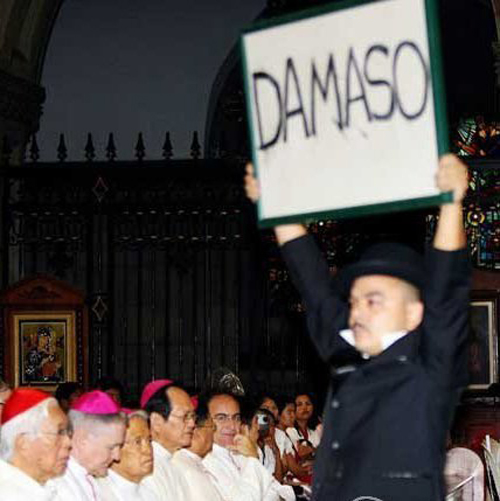 "Carlos Celdran holds up a placard that reads ""DAMASO"" in front of a row of Catholic Bishops in the middle of mass at Manila Cathedral."