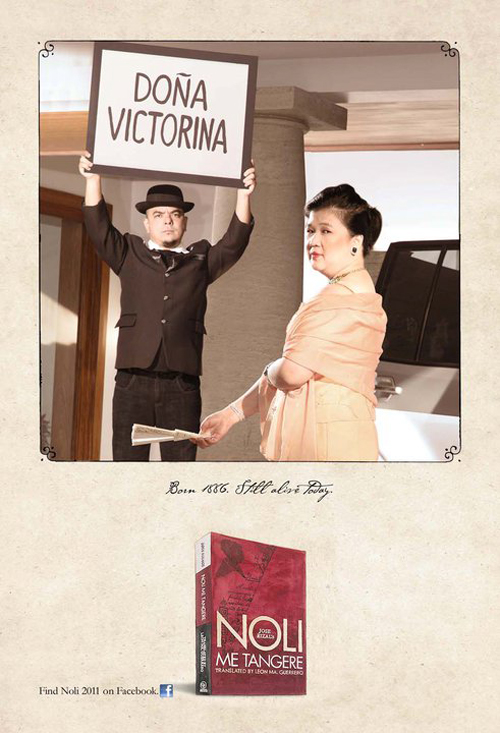 "Celdran holds up a placard that says ""Dona Victorina"" the a well dressed lady standing with a smug expression in the foreground."