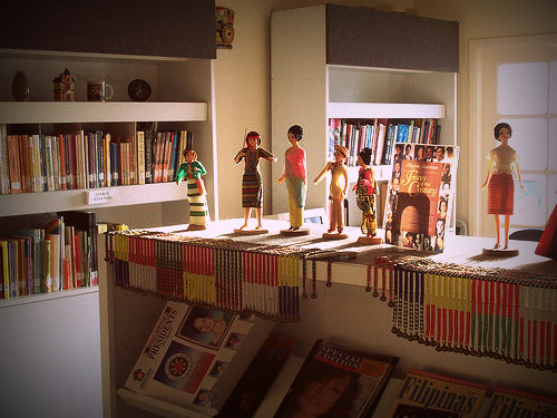A section of the Filipino American Library with books on shelves, decorated with Filipino dolls and beads.