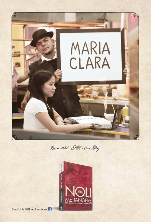 "Celdran holds a placard that says ""Maria Clara"" with a girl on a laptop in the foreground."