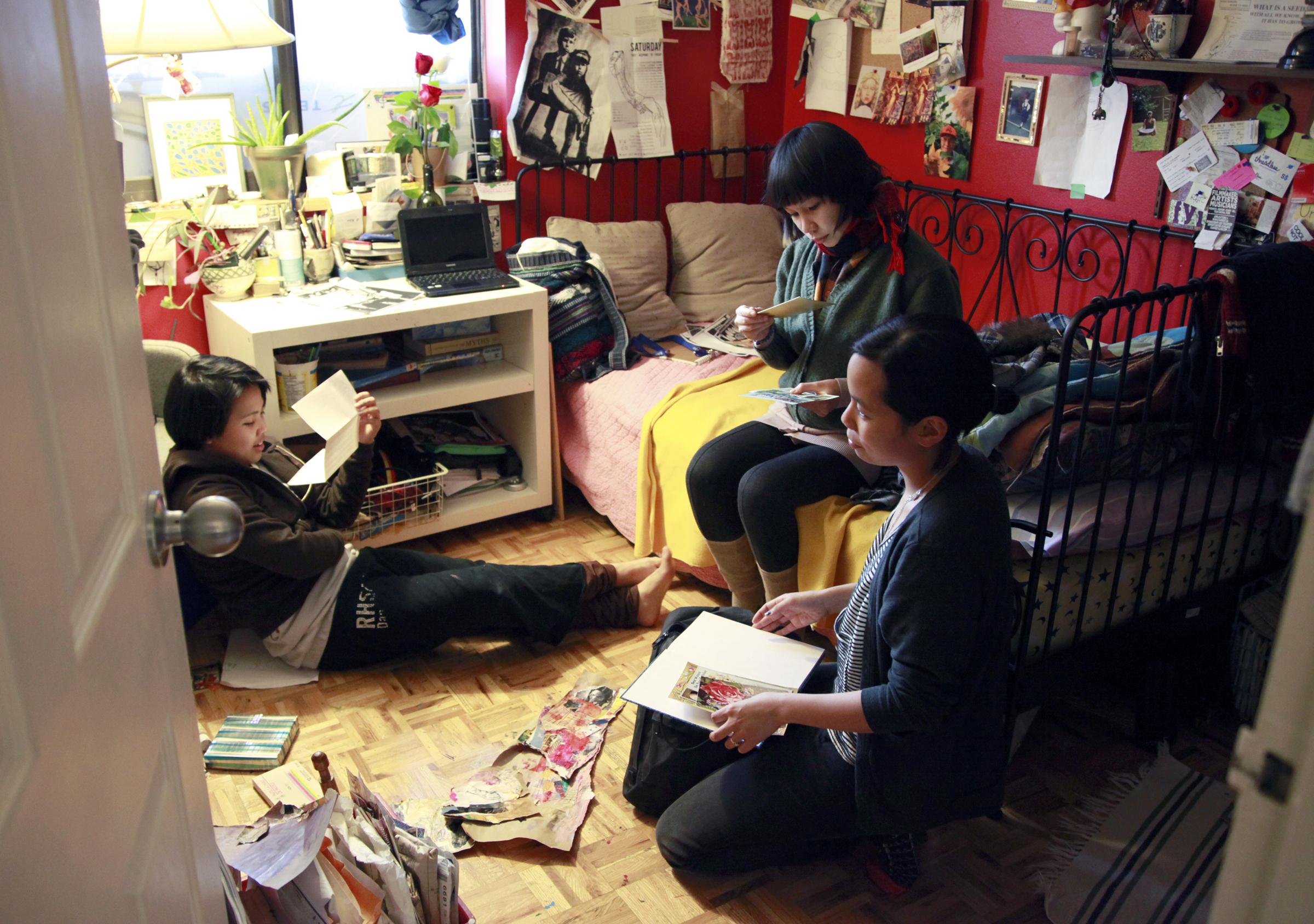 The CLUTCH girls hanging out with Casey their coordinator, in a bedroom with all their artwork laid out on the floor