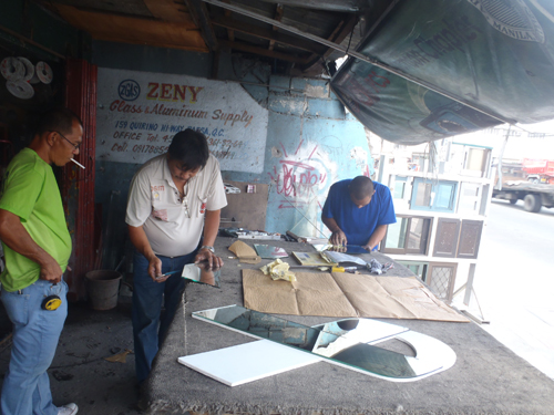 three men sanding down glass at a shop in manila