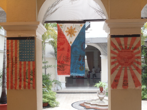 A view of the Philippine, American, and Japanese flags at half mast