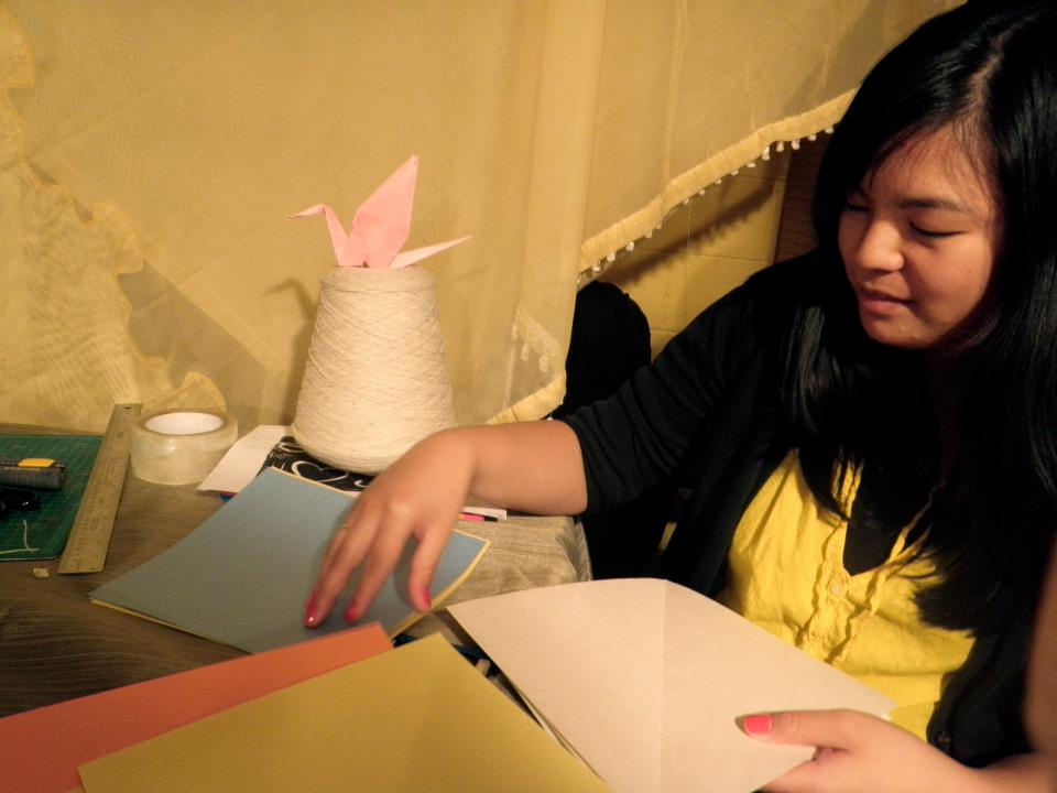 Clutch Vol 4 Maureen working on paper cranes for AHON