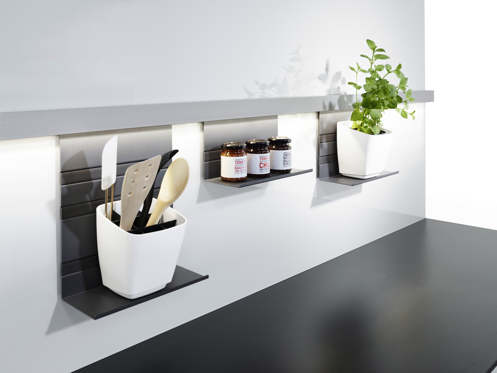 LINERO MosaiQ is flexible and versatile, offering users a huge choice for configuring the space between the countertop and the wall cabinets.   The multi-functional, anodized aluminium rail can be either screwed or glued to the wall, making it ideal for glass backsplashes too.     The MosaiQ shelf elements are hung from below the rail or clipped on above it. The shelf elements come in a choice of three heights and two widths. Horizontal strips on the shelf elements accentuate the design. The three sophisticated grey tones of the matte, tactile coating were chosen in consultation with experts at a well-known design institute. Functional elements include various hooks and single and double roll holders. There is also a specially designed knife block and small pots with an angled bases to hold, for example, a pot of herbs. LINERO MosaiQ has been launched with ten core applications which users can mix and match as they please. It's the perfect way to make the most of the midway space in kitchens and bathrooms.