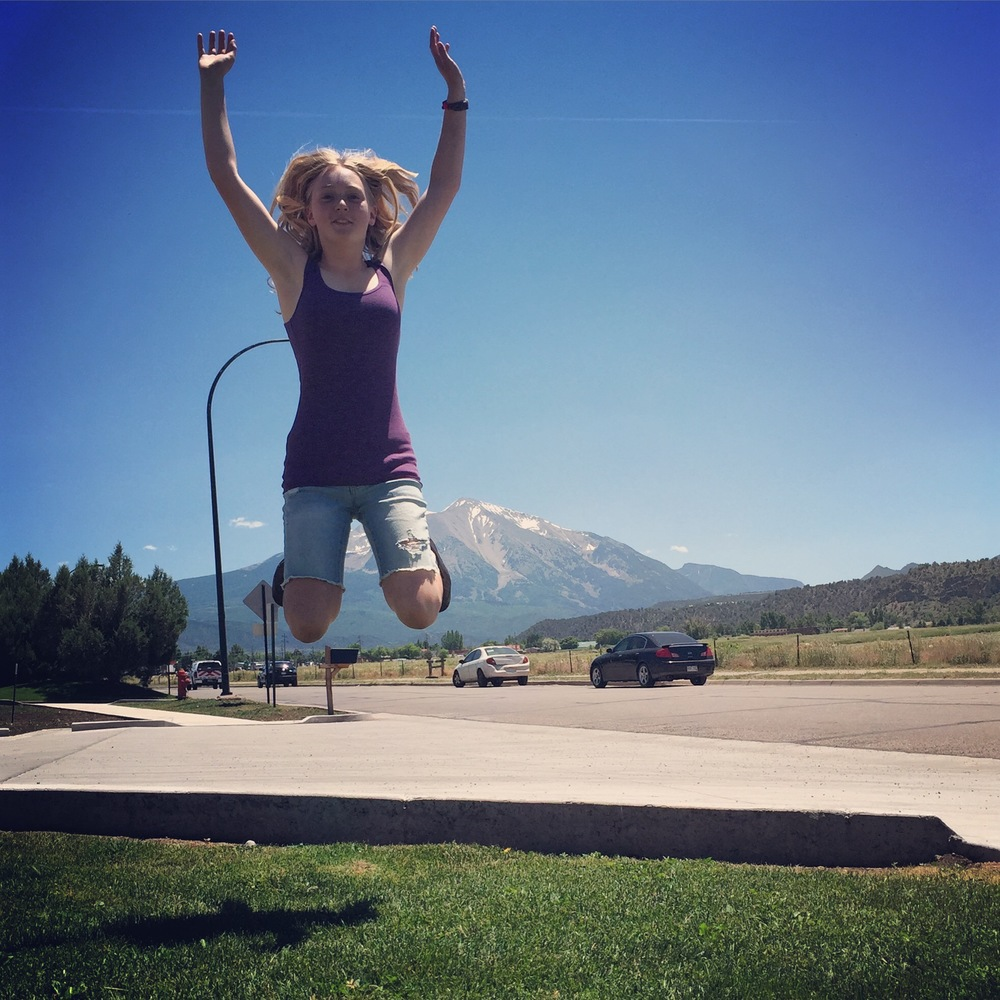 Victoria jumps for joy about her summer internship in front of beautiful Mt. Sopris.
