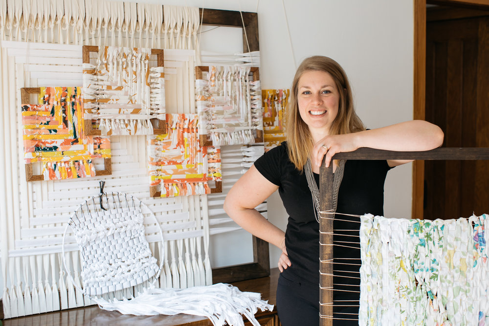 Jamie in her home surrounded by woven textile art made with recycled materials.