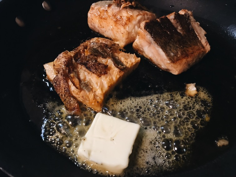 Then put butter on it and garlic. Scoop some butter and shower it on to the fish. Flip it to the skin side one last time on low heat.