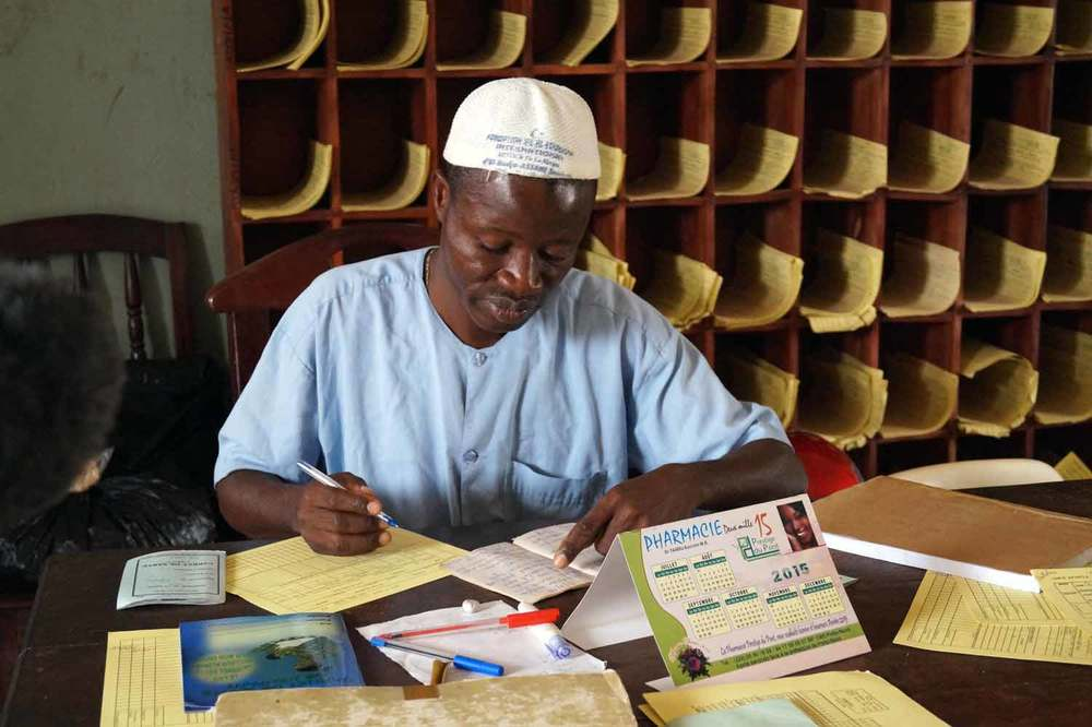 A health worker sorts through paper records. Source: VaxTrac.com
