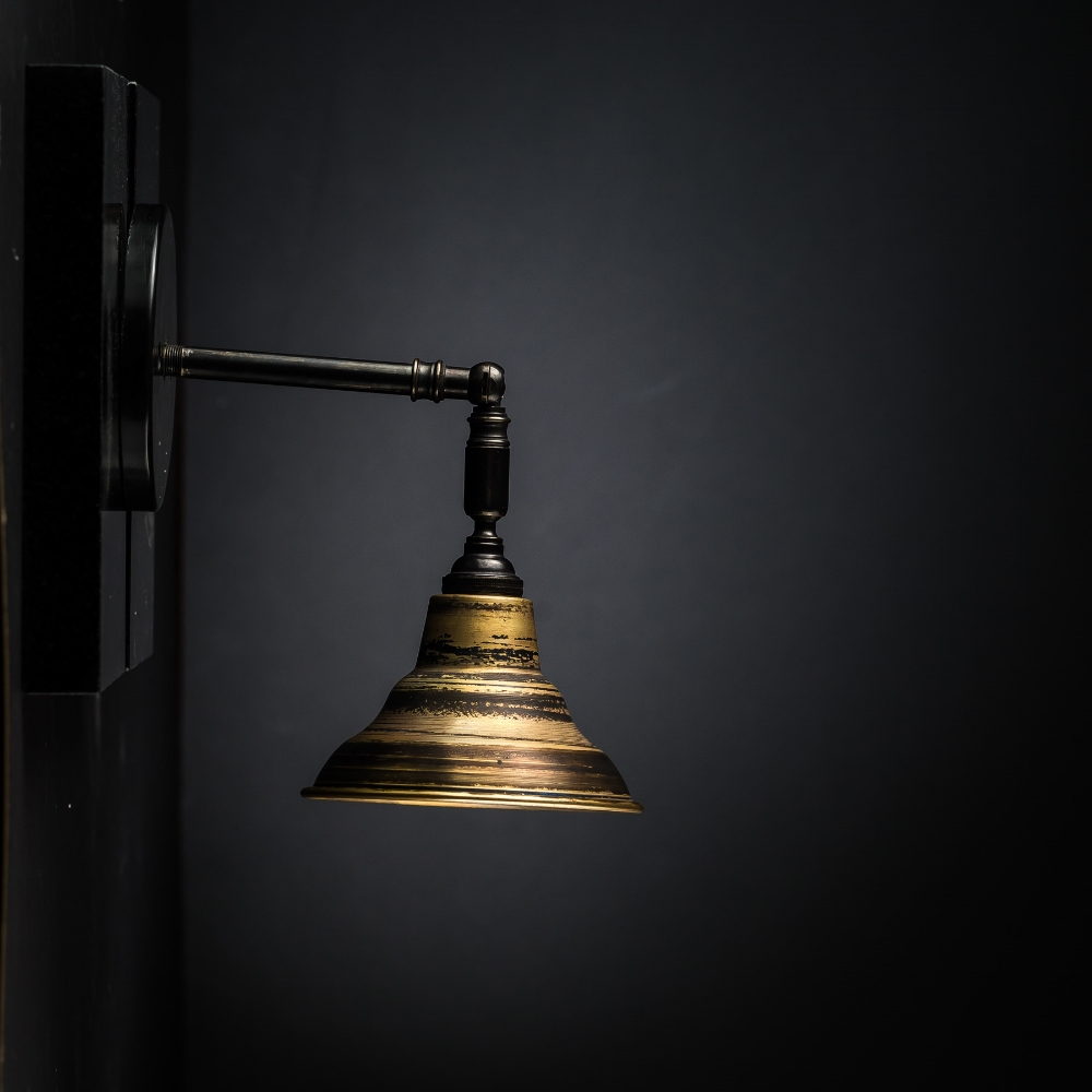 Distressed turned bronze armed wall light.jpg