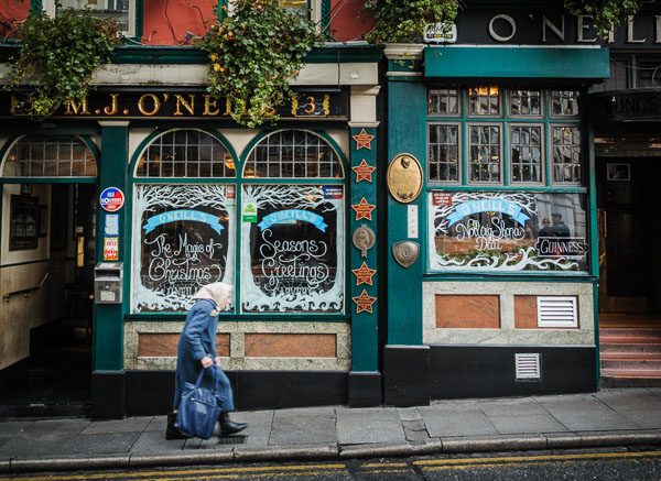 Old Lady walking by O'Neill's Pub in Dublin
