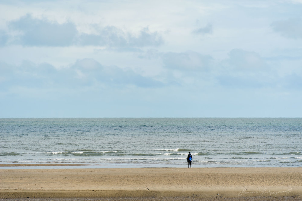 Person stands on the shore at Malahide Beach