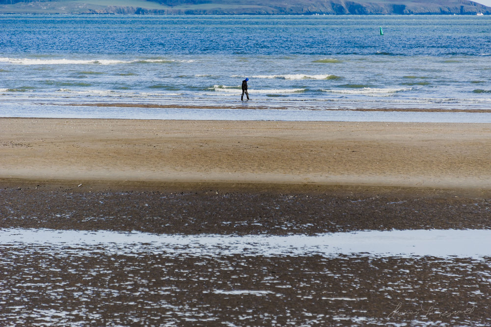 Person walks on the beach at Malahide