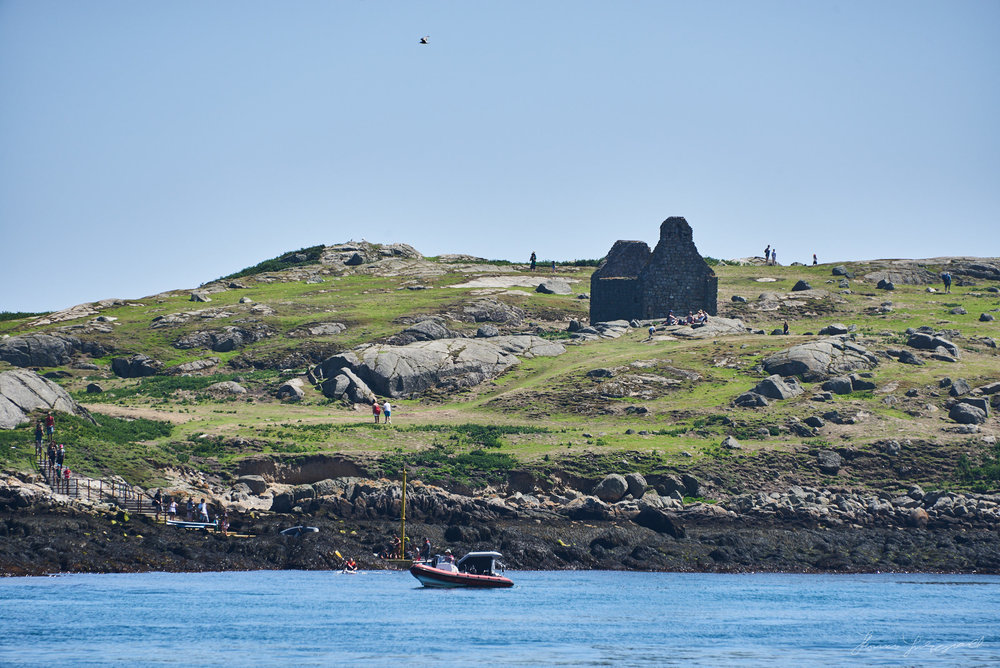 Looking out towards Dalkey Island on a bright summers day from Colliemore Harbour in Dalkey. On the island you can see boats moored and people exploring the Island.