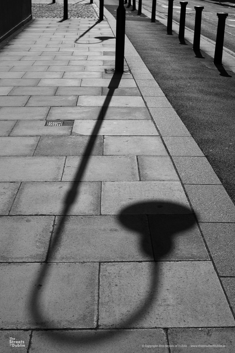 Shadows of a street lamp on paving