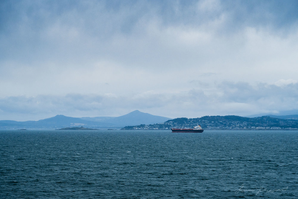 A cargo ship in Dublin bay with wicklow and Dublin in the background
