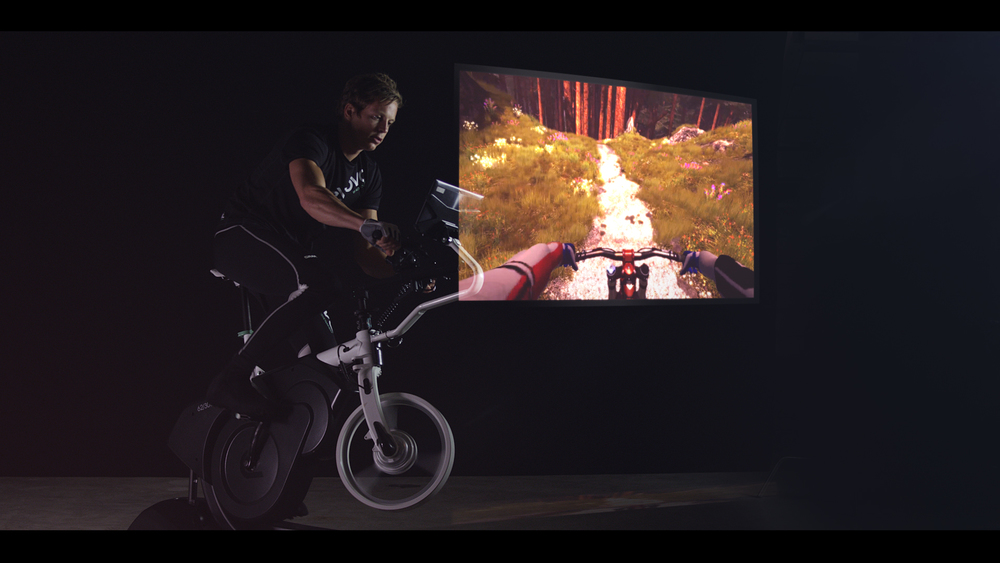 """Bike incline, pedal resistance and movement automatically corresponds to immersive 3D visuals.User can choose from a range of pre-loaded tracks and routes, all operated through a 15.6"""" touch screen."""