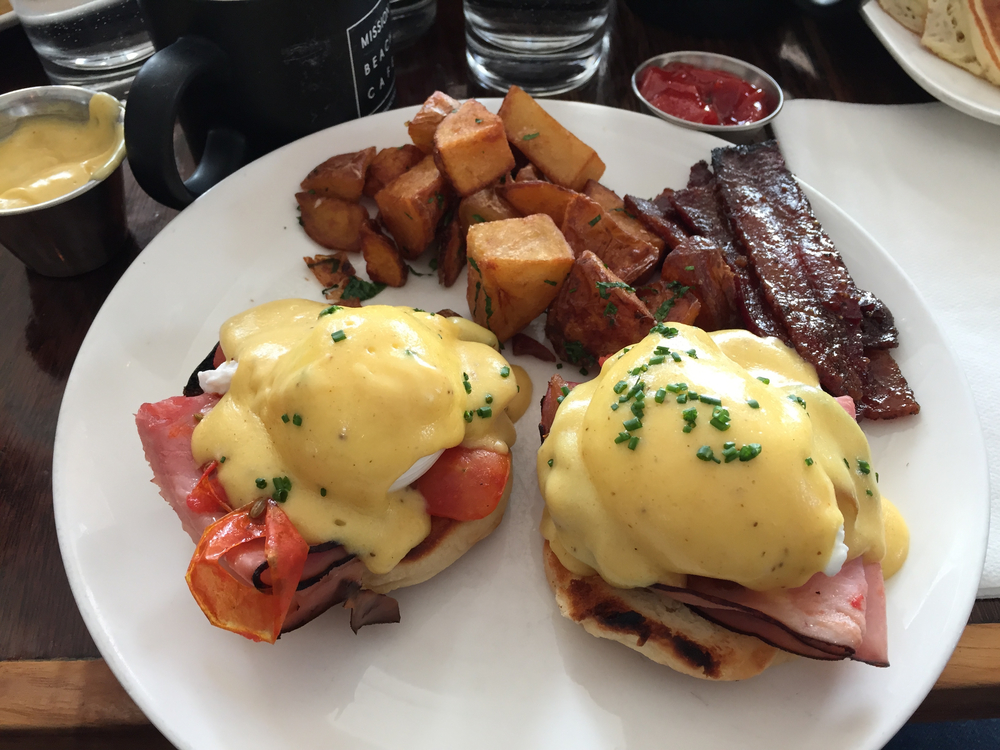 Eggs benedict with black forest ham and roasted tomatoes + caramelized pepper bacon on the side.