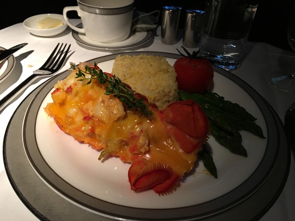 Lobster Thermidor with buttered asparagus, slow-roasted vine-ripened tomato, and saffron rice