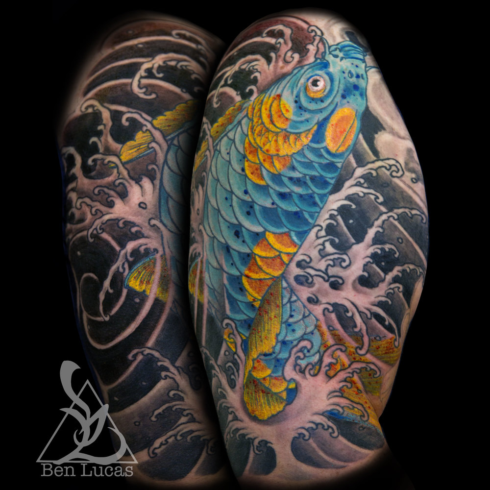 Blue and Gold koi fish swimming up and jumping out of fingerwaves water with pink green and yellow chrysathemum done by Ben Lucas at Eye of Jade in Chico, CA, U.S.A.