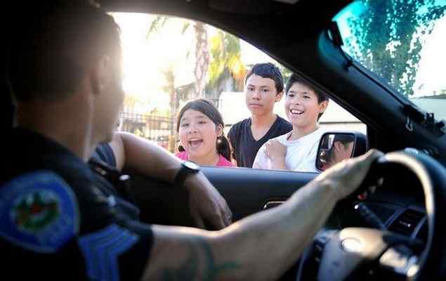 San Bernardino police Sgt. Chris Gray chats with Rene Maldonado, 13, and Isaiah Bustamante, 11, Sept. 25, 2016 in San Bernardino. Micah Escamilla/Staff Photographer