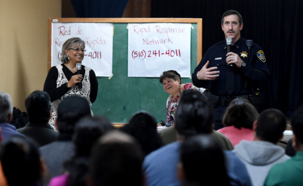 Mike Reilly, a lieutenant with the Oakland Police Department, draws smiles from certified court interpreter Elizabeth Dantes, of Napa, left, and Emma Paulino, of Oakland Community Organizations, when he tells the group of mostly hispanic individuals that it makes him nervous too when he sees a police officer while he speaks at St. Jarlath Catholic Church in Oakland, Calif., on Sunday, March 19, 2017. (Susan Tripp Pollard/Bay Area News Group)
