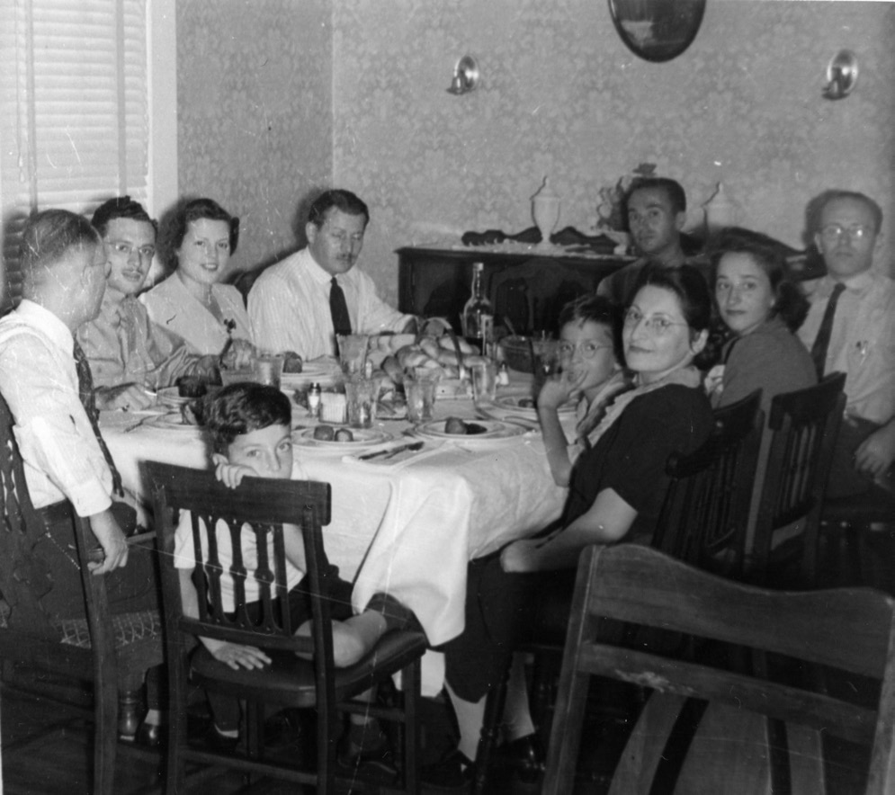 A family dinner in 1941 or 1942 with guests from Camp Shelby, with my father at far left, then (clockwise) Captain and Mrs. Norman Gottlieb, unknown guest, empty chair where the photographer-soldier was sitting, another soldier, Norman, Fay, Milton, my mother, and me.