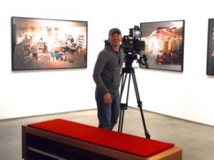 Luc films the photographs in Lori's show at ClampArt.