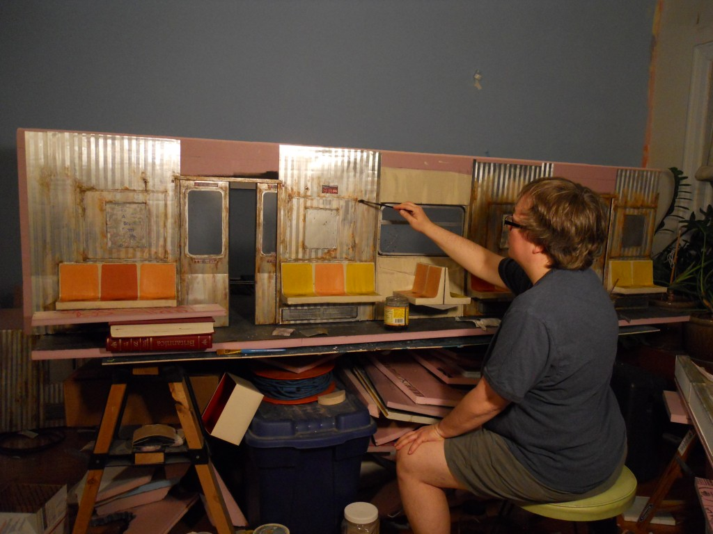Subway seats attached to back wall of model. Lori fine tunes the dirty and rusty finish.