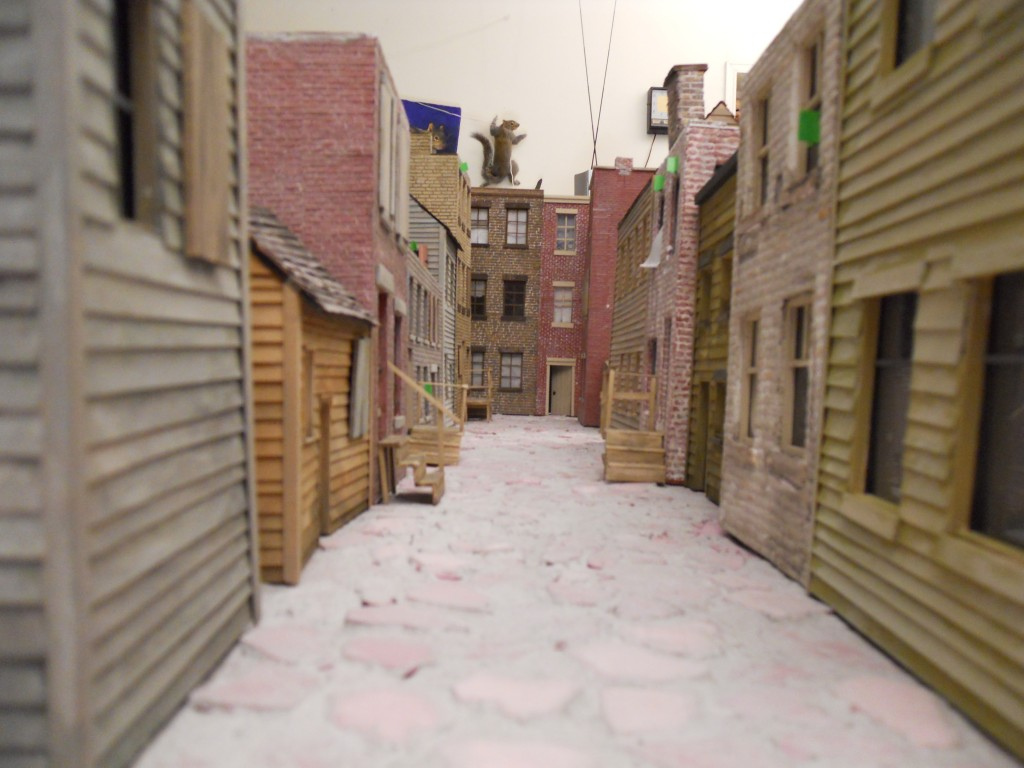 Early stage of alley. Buildings are all scratch-built. A rare, hovering giant squirrel looms in the distance.