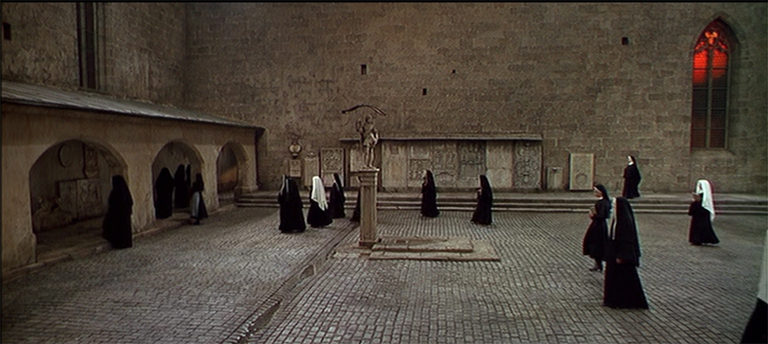 The next scene deals with light and shadow, or the absence of light. As the nuns walk into the Abbey they are walking directly towards the camera. At the end of this cut, two nuns walk right into the camera, (or it appears so.) The next cut the scenes switches to a darker shot showing the nuns' from the back as they are now inside and taking their seats. The transition from light to backlight is a powerful tool to use in still photography. Try shooting your next images using front light and then letting your subjects become silhouettes using backlight. Once you master using this you will enjoy photography even more as you make more powerful images.