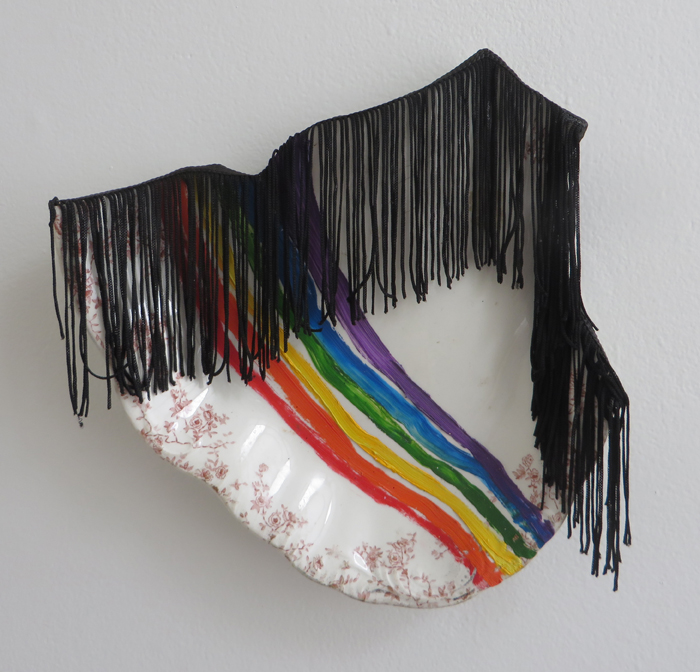 "heather garland // rainbow brite iud // 2016 // oil and fringe on broken found ceramic platter // 10"" x 10"""