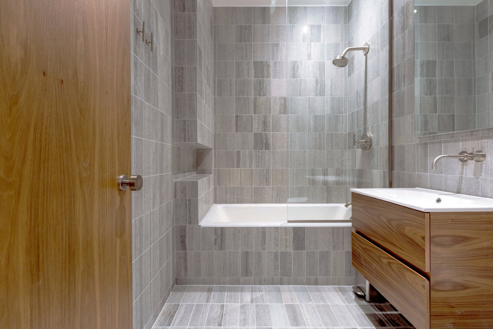 Grey marble and walnut bathroom.